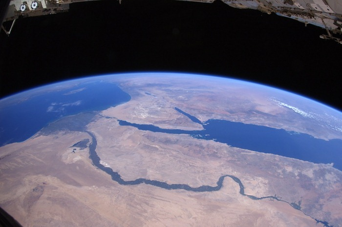 Over the Sahara desert, approaching the ancient lands and thousand-year history. River Nile flows through Egypt by the Pyramids of Giza in Cairo. Further, the Red Sea, Sinai Peninsula, Dead Sea, Jordan River, as well as the island of Cyprus in the Mediterranean Sea and Greece on the horizon.