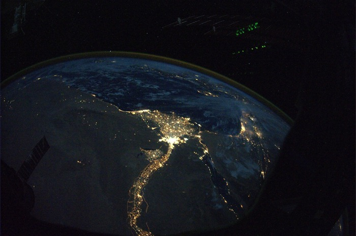 Night view of the River Nile, stretching like a snake through Egypt to the Mediterranean, and Cairo, located in the Delta. Far away in this picture, one can see the Mediterranean Sea.