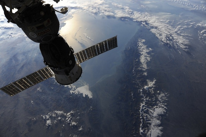 Module Union 23C Olympus docked with the ISS . When our work ends here, we go back home to Earth. We fly over the snow-capped peaks of the Caucasus. The rising sun is reflected from the Caspian Sea.