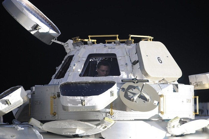 """Dome"" on the side of Nadir station gives a panoramic view of our beautiful planet. Fedor made the picture from the window of the Russian docking compartment. In this photo I'm sitting in the dome, preparing the camera for our evening flight over Hurricane Earl."